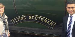 Judith Kelly and Rishi standing next to the Flying Scotsman steam locomotive